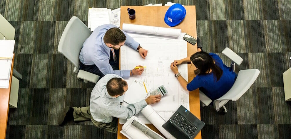 Tampa employee rights lawyer ensures all workers are treated fairly., including workings like these 3 people reviewing architectural plans at a table.
