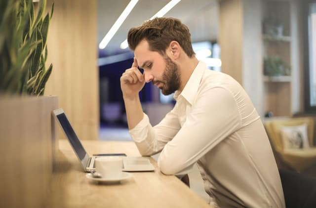 Were you given termination without cause? You may feel like this dejected man who sits at his laptop, leaning his head on one hand.